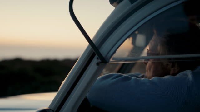 senior man sitting in his car enjoying sunset - happiness stock videos & royalty-free footage