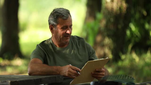 älterer mann sitzt im park - sitz stock-videos und b-roll-filmmaterial
