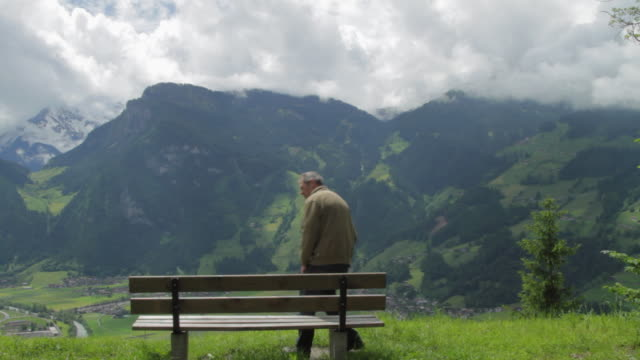 ws senior man sitting on bench with mountain in background / mayrhofen, zillertal, austria - one senior man only stock-videos und b-roll-filmmaterial