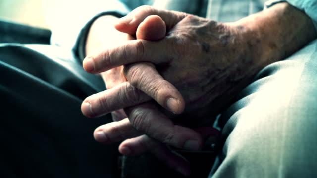 vidéos et rushes de senior homme assis sur la chaise avec ses mains de croix - plan très rapproché