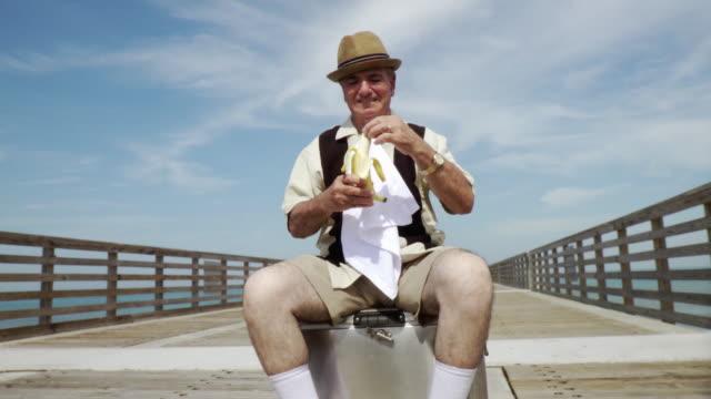 MS PAN TU Senior man sitting on cooler eating banana / Jacksonville Beach, Florida, USA