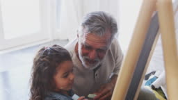 Senior man sitting on the floor drawing with his granddaughter on a blackboard, elevated view