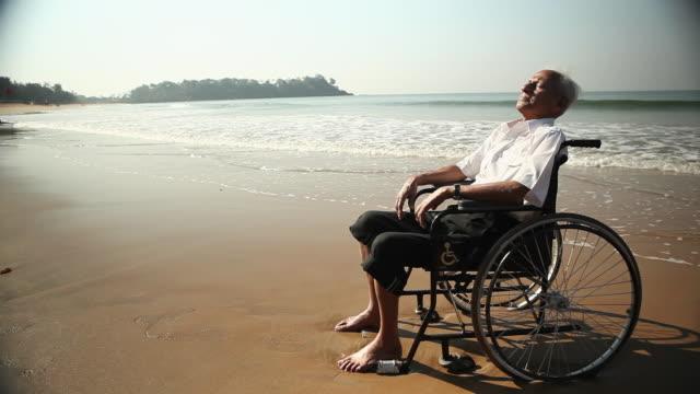 vidéos et rushes de senior man sitting on the wheelchair on the beach - ensoleillé
