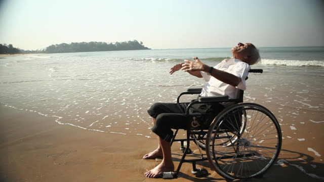 stockvideo's en b-roll-footage met senior man sitting on the wheelchair on the beach - afhankelijkheid