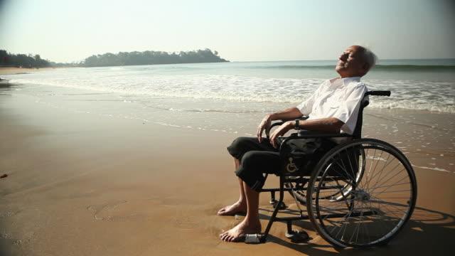 Senior man sitting on the wheelchair on the beach