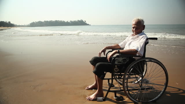 senior man sitting on the wheelchair on the beach - wheelchair stock videos and b-roll footage