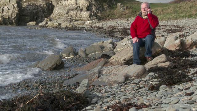年配の男性が座っている岩の海岸に携帯電話を使用して