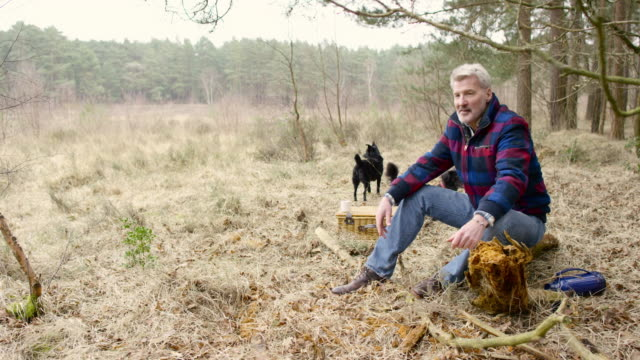 Senior man sitting with his dogs enjoying the wilderness from his campsite