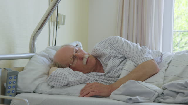 senior man sleeping comfortably on hospital bed - napping stock videos & royalty-free footage