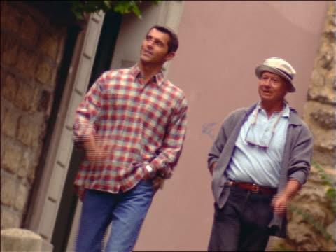 senior man + son walking along sidewalk + pointing to something offscreen / france - adult offspring stock videos & royalty-free footage