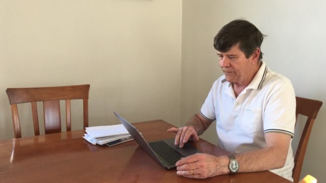 Senior man sorts his financial bills and works on a laptop