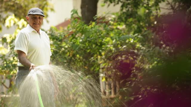 Senior man spraying water on plants in a lawn