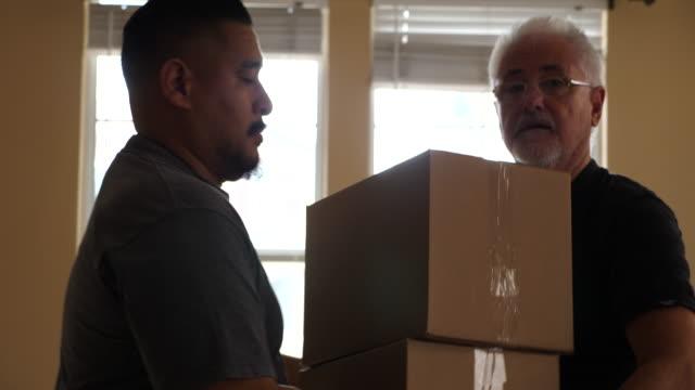 cu ts senior man stacking boxes in living room on moving day - flyttlåda bildbanksvideor och videomaterial från bakom kulisserna