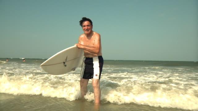 SLO MO MS Senior man standing in water holding surfboard, Jacksonville, Florida, USA