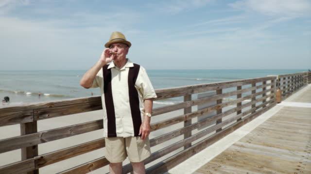 WS Senior man standing on pier smoking cigar / Jacksonville Beach, Florida, USA