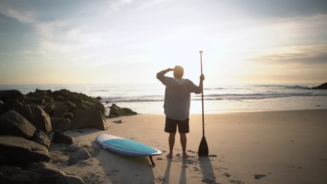 ws senior man standing on the beach with his paddleboard at sunset - cap stock videos & royalty-free footage