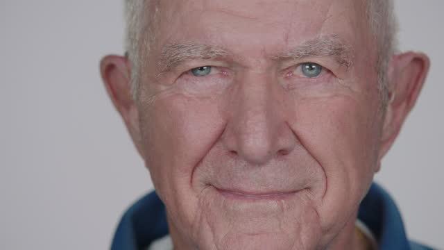 cu slo mo. senior man stares into camera and smiles. - uomini anziani video stock e b–roll