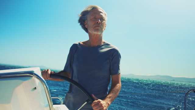senior man steering yacht against sky in vacation - helm stock videos and b-roll footage