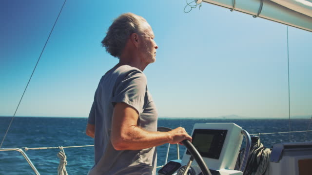 senior man steering yacht against sky in vacation - helm stock videos & royalty-free footage
