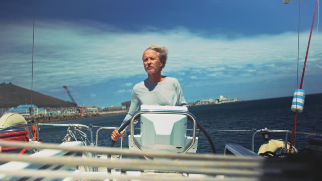 senior man steering yacht in summer against sky - helm stock videos and b-roll footage