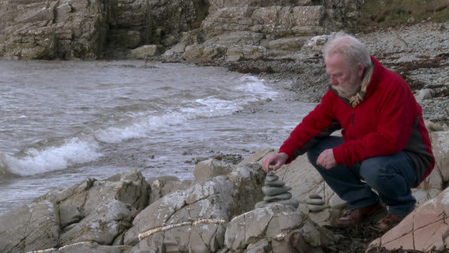 senior man stone staking on a rocky shore - johnfscott stock videos & royalty-free footage