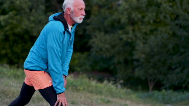 vídeos y material grabado en eventos de stock de senior hombre estiramiento antes de correr - pasatiempos