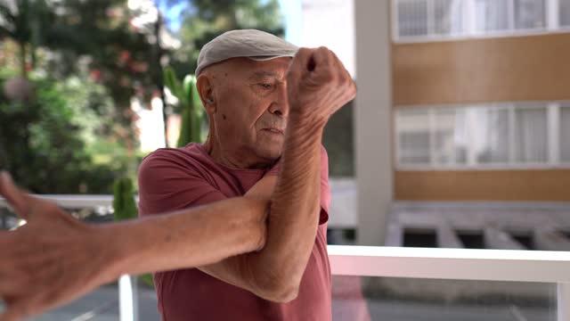 senior mann streckt sich auf dem balkon - menschliche gliedmaßen stock-videos und b-roll-filmmaterial