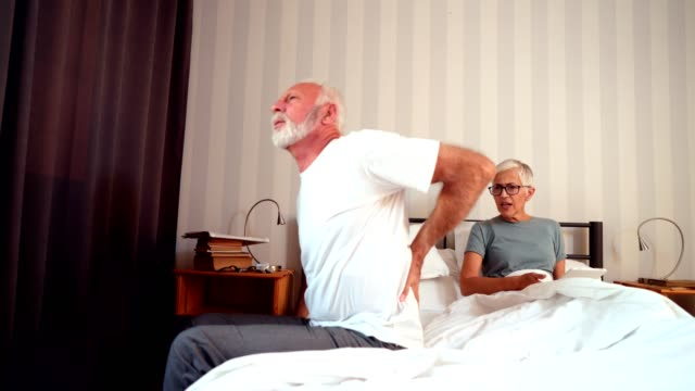 Senior man suffering from back pain getting out of bed
