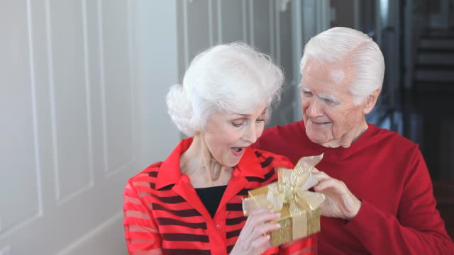MS TD Senior man surprising wife with gift in hallway of home, Eastville, Virginia, USA