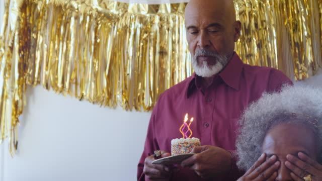 senior man surprising woman with birthday cake - birthday candle stock videos & royalty-free footage