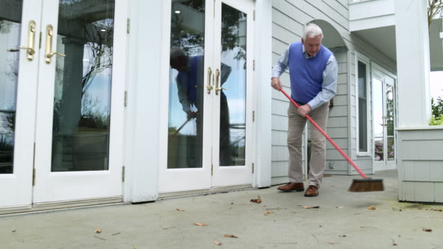 Senior man sweeping leaves on porch