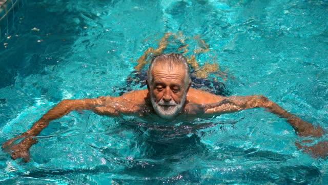 senior man swimming in  swimming pool - standing water stock videos & royalty-free footage