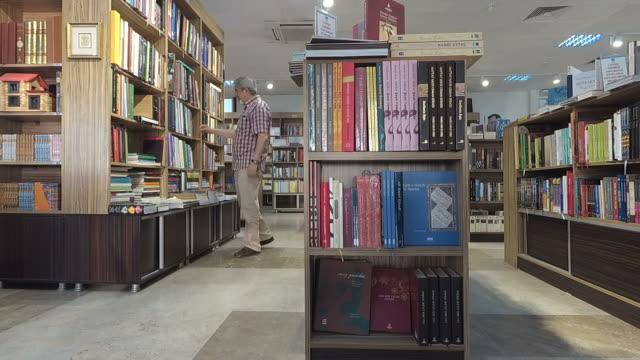 stockvideo's en b-roll-footage met senior man nemen een boek van een bibliotheek plank - leesbril