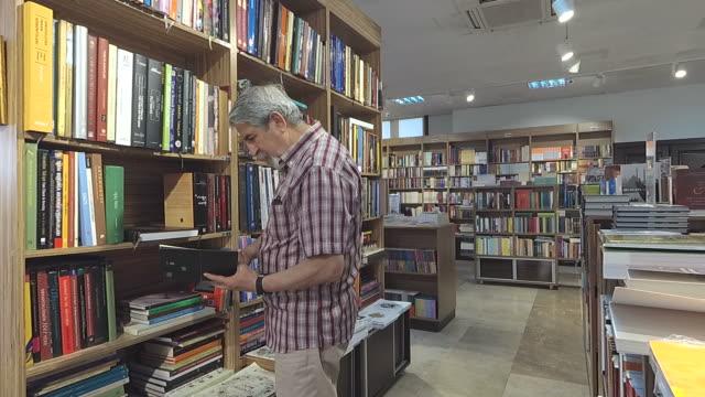 年配の男性が図書館の棚から本を取って - 公共図書館点の映像素材/bロール