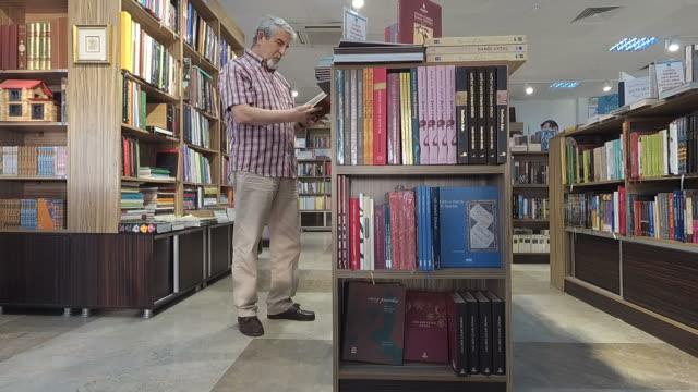 Senior man taking a book off a library shelf