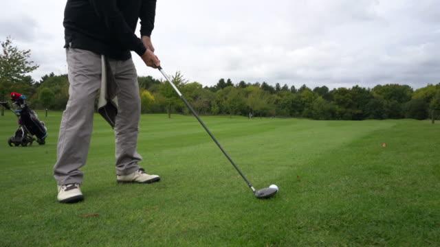 vídeos de stock, filmes e b-roll de a senior man taking a swing on the fairway and hitting the green. - bolsa de golfe