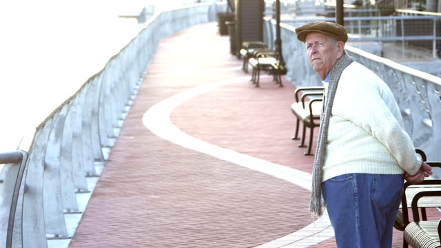 senior man taking a walk on a city waterfront - hands behind back stock videos and b-roll footage