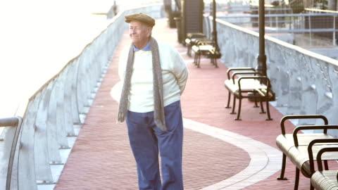 senior man taking a walk on a city waterfront - white hair stock videos & royalty-free footage