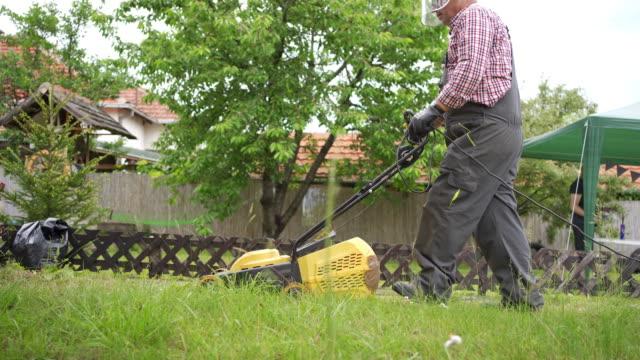 vidéos et rushes de homme aîné prenant soin de l'herbe de surgrowing dans sa cour - pelouse