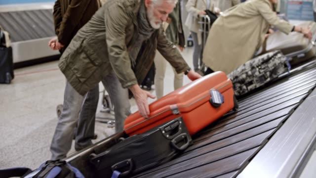 LD Senior man taking his travel bag off the baggage carousel at the airport