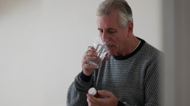 senior man taking medicine - prescription stock videos and b-roll footage