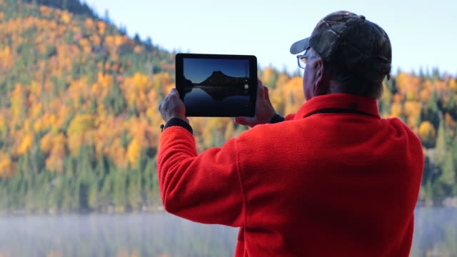 Senior Man Taking Picture of Lake Nature with Digital Tablet