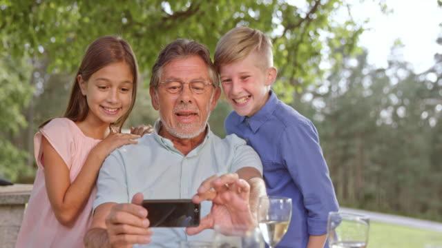 slo mo senior man taking selfies with his two grandkids - memories stock videos & royalty-free footage