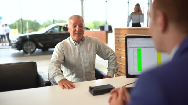 vídeos de stock, filmes e b-roll de idoso fala sobre termos de compra de carro com gerente em concessionária de carros - vender