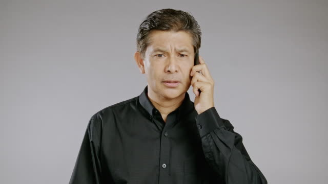 senior man talking, mobile phone, investigating, isolated in grey background. asian man in black shirt. - black shirt stock videos & royalty-free footage