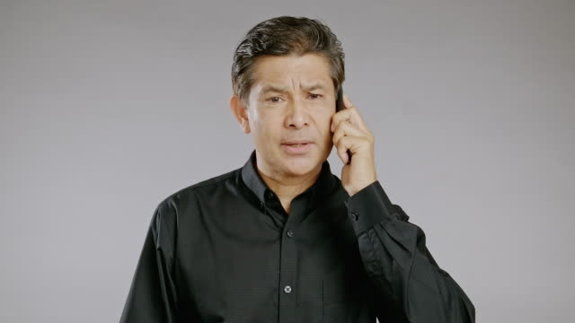senior man talking, mobile phone, serious, isolated in grey background. asian man in black shirt. - black shirt stock videos & royalty-free footage
