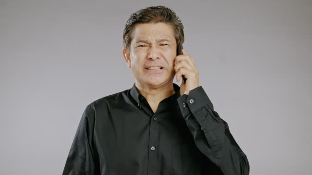 senior man talking, mobile phone, shouting, very angry isolated in grey background. asian man in black shirt. - black shirt stock videos & royalty-free footage
