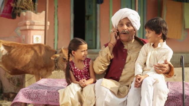 senior man talking on a mobile phone with his grandchildren  - dhoti video stock e b–roll
