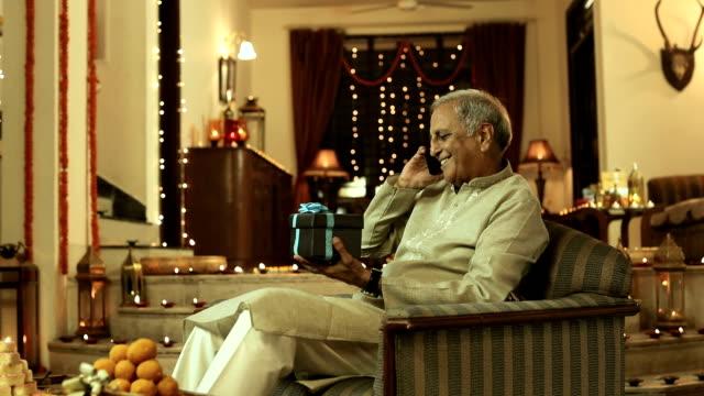 Senior man talking on mobile phone at home, Delhi, India