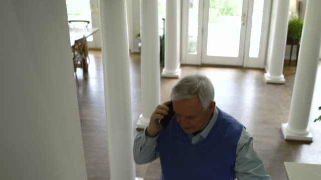 Senior man talking on phone while walking up stairs at home